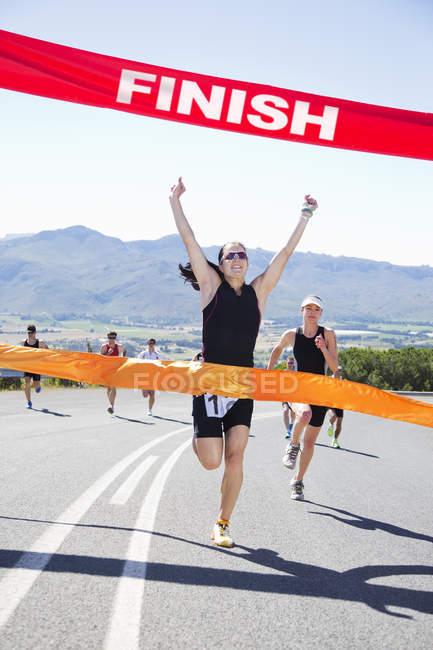 Runner crossing race finish line — Stock Photo