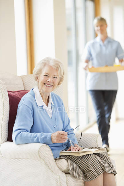 Older woman smiling in armchair — Stock Photo