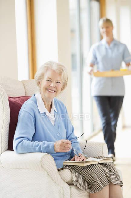 Пожилая женщина, улыбающаяся в кресле — стоковое фото