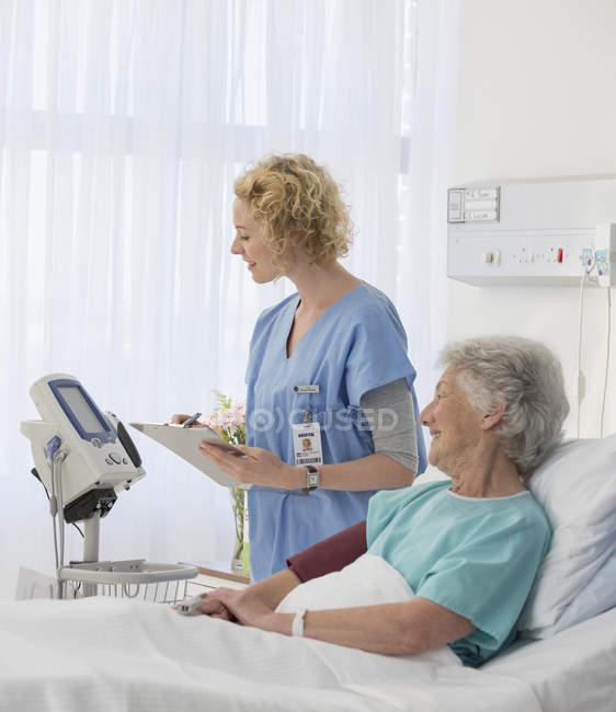Krankenschwester überprüft Geräte im Krankenzimmer eines alternden Patienten — Stockfoto