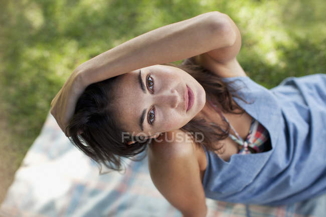 Overhead portrait of sexy woman sitting on blanket in grass — Stock Photo