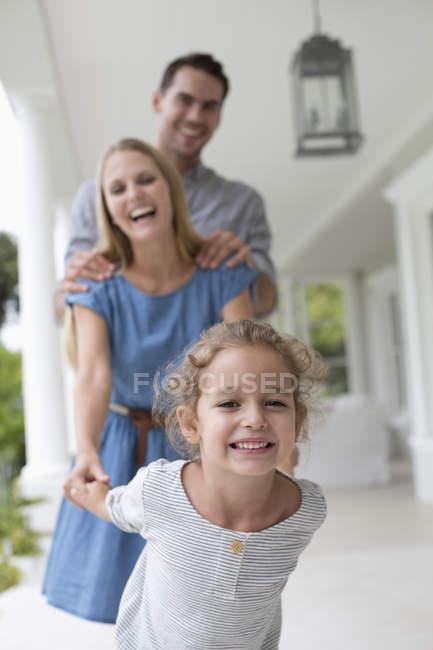 Молода сім'я разом грають на ганку — стокове фото