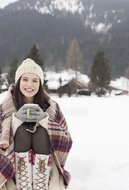 Portrait of smiling woman drinking coffee in snowy field — Stock Photo