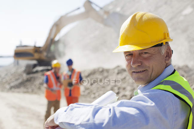 Businessman wearing hard hat in quarry — Stock Photo