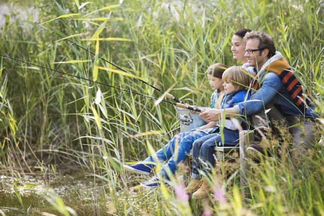 Pêche familiale ensemble dans l'herbe haute — Photo de stock