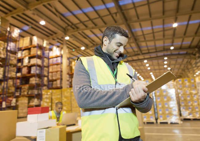 Trabajador en portapapeles en almacén - foto de stock