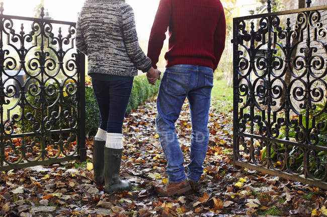 Couple holding hands outdoors, rear view — Stock Photo