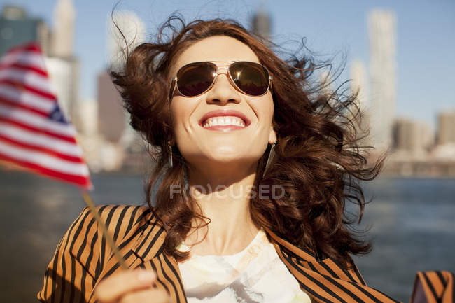 Smiling woman waving American flag — стокове фото