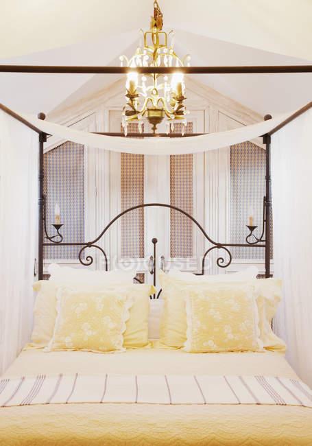Lustre sobre quatro cama de cartaz com lençóis amarelos — Fotografia de Stock