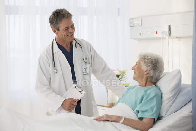 Doctor talking to elderly patient in hospital — Stock Photo