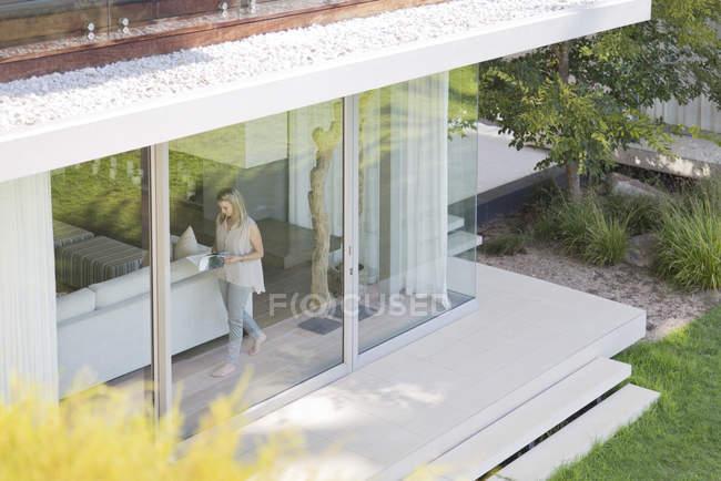 Женщина, прогуливаясь по окна в доме — стоковое фото