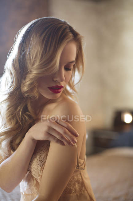 Blond woman wearing lingerie in bedroom — Stock Photo