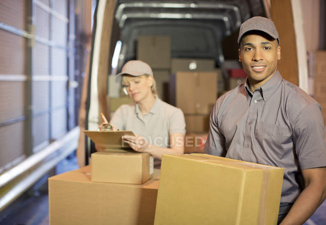 Delivery people loading boxes into van — Stock Photo