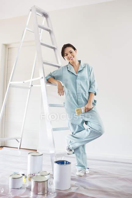 Умелая кавказская женщина улыбается и рисует комнату — стоковое фото