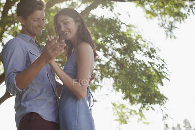 Sorrindo casal de mãos dadas debaixo da árvore — Fotografia de Stock