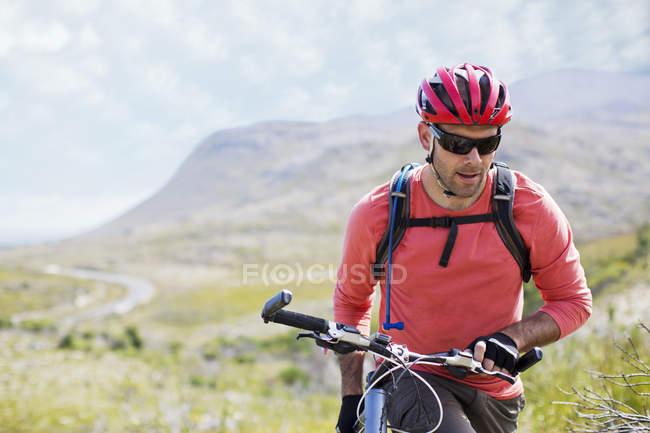 Homme marche à vélo dans le paysage rural — Photo de stock