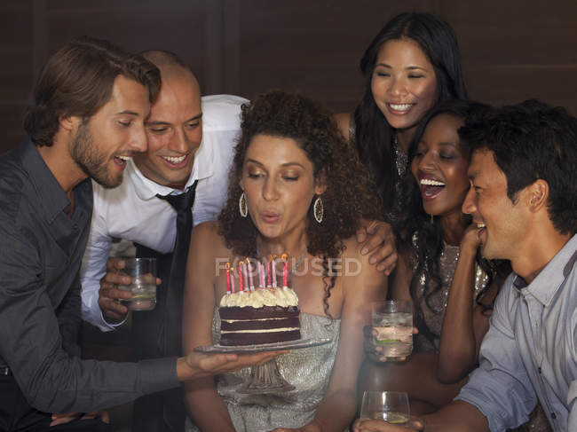 Woman blowing out birthday candles at party — Stock Photo