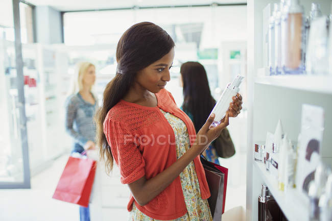Woman examining skincare product in drugstore — Stock Photo