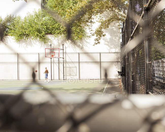 Homem jogando basquete na quadra urbana — Fotografia de Stock