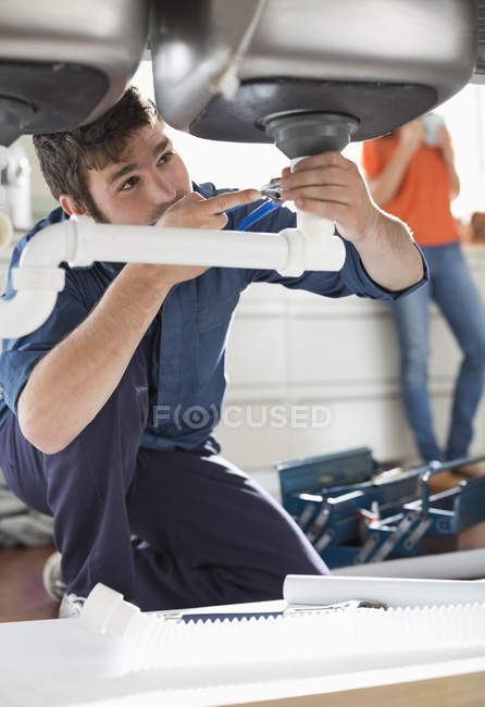 Plumber working on pipes under sink — Stock Photo