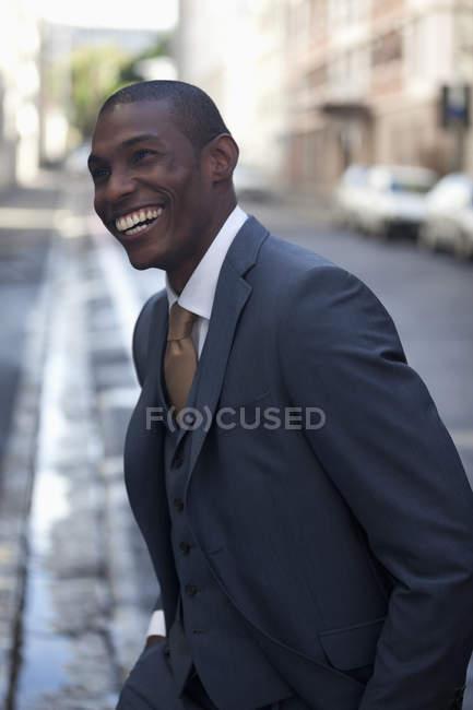 Happy businessman walking in street — Stock Photo