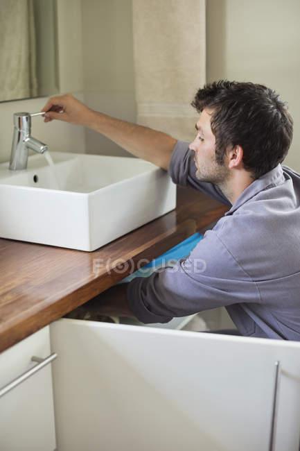 Искусный кавказский сантехник, работающий на раковине в ванной — стоковое фото