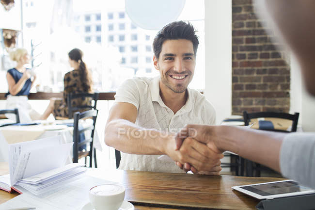Empresários apertando as mãos no café — Fotografia de Stock