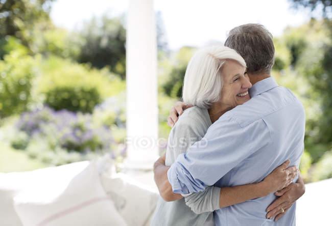 Старшая кавказская пара обнимается на патио — стоковое фото