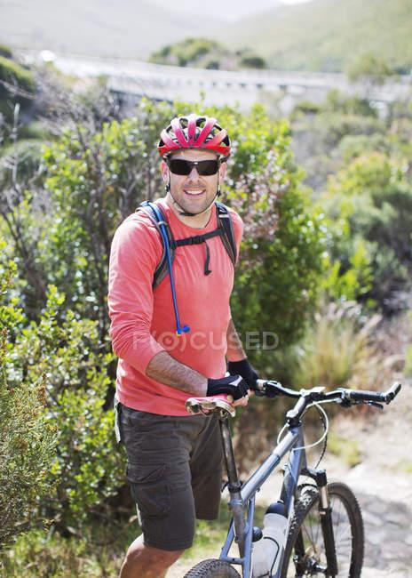 Уверенный кавказский горный велосипедист на грунтовой дорожке — стоковое фото