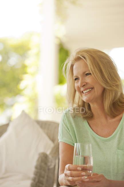 Усміхаючись жінка питної води на внутрішній дворик — стокове фото