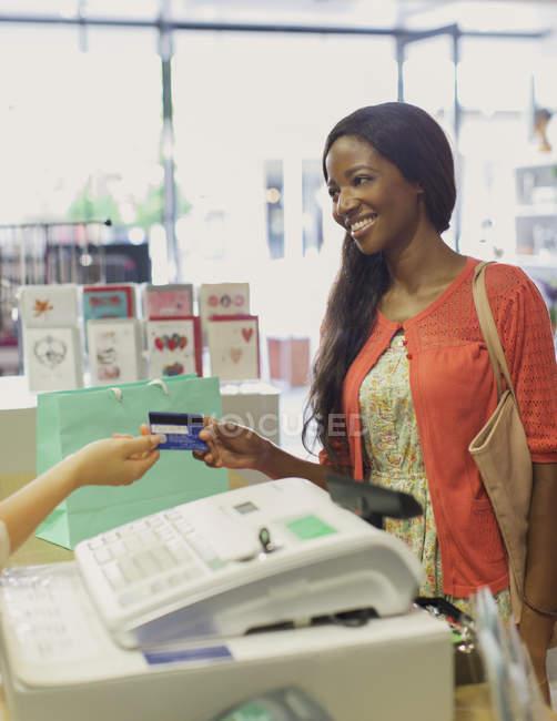 Женщина, платящая кредитной картой в аптеке — стоковое фото