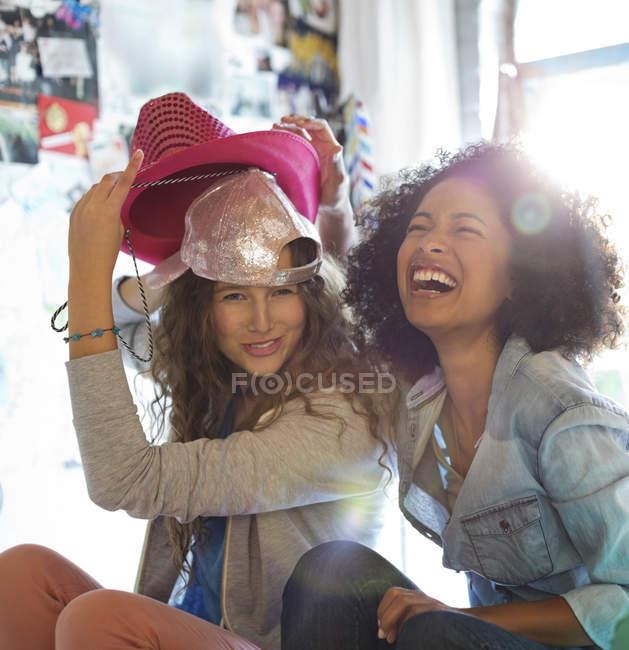 Jovens mulheres felizes brincando com chapéus no quarto — Fotografia de Stock