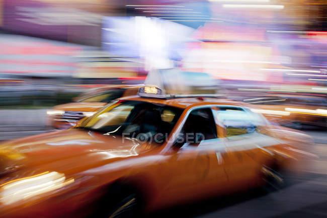 Размытый вид на такси на городской улице ночью — стоковое фото