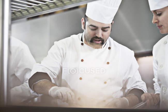 Chefs cooking in restaurant kitchen — Stock Photo