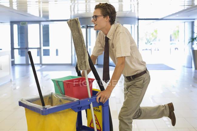 Empresário empurrando carrinho de limpeza no escritório — Fotografia de Stock