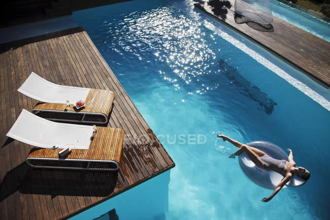 Mulher flutuando no anel inflável na piscina de luxo — Fotografia de Stock
