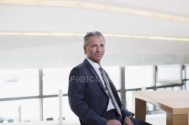 Портрет улыбаясь бизнесмена за столом — стоковое фото