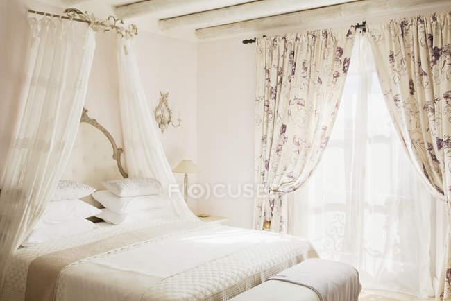 Cama con dosel en el dormitorio de lujo - foto de stock