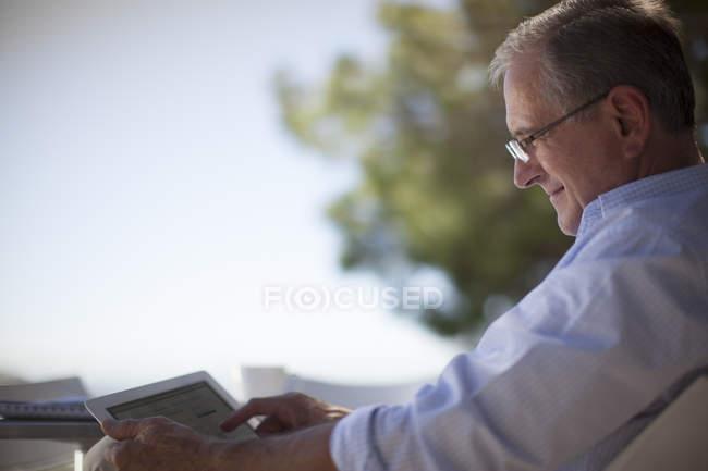 Homme plus âgé utilisant un ordinateur tablette à l'extérieur — Photo de stock