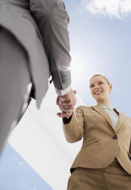 Homme d'affaires et femme d'affaires serrant la main sous le ciel bleu — Photo de stock