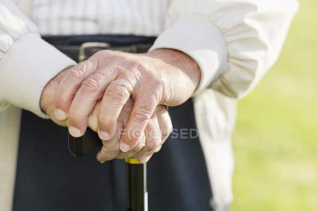Крупним планом літньою людиною руки на тростини — стокове фото