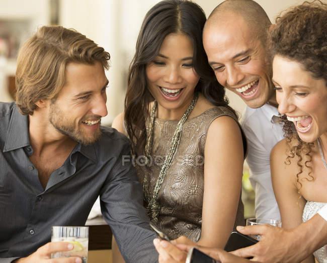Jovens amigos atraentes usando telefones celulares na festa — Fotografia de Stock