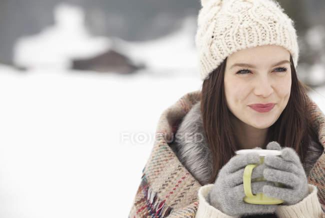 Крупный план улыбающейся женщины в вязаной шляпе и перчатках, пьющей кофе на снежном поле — стоковое фото