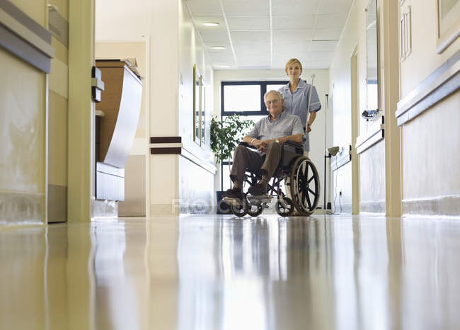 Nurse wheeling older patient in hospital — Stock Photo