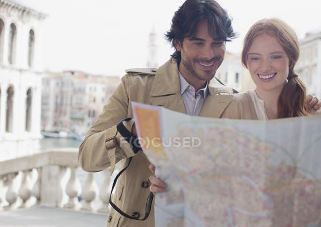 Улыбающаяся пара смотрит вниз на карту Венеции — стоковое фото