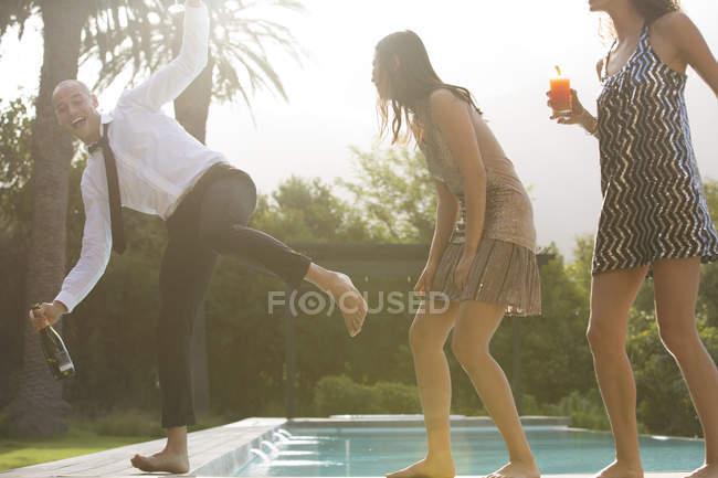 Amici che bevono a bordo piscina — Foto stock