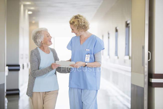 Nurse and senior patient talking in hospital corridor — Stock Photo