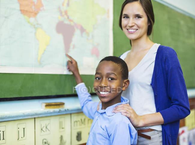 Учитель з афро-американських студентів, використовуючи мапу світу — стокове фото