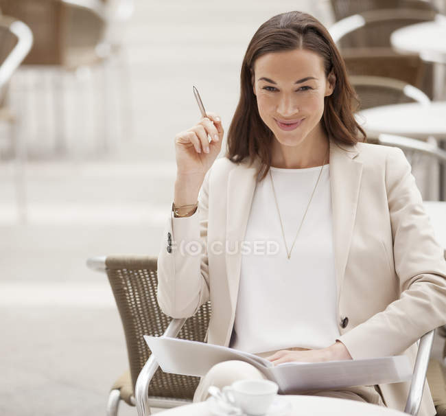 Portrait of smiling businesswoman with paperwork at sidewalk cafe — Stock Photo