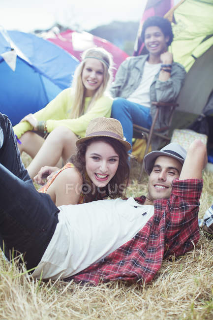 Portrait of friends hanging out outside of tents at music festival — Stock Photo
